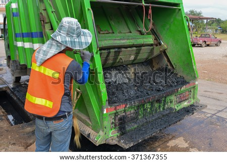 Worker of urban municipal  loading waste water and garbage to the refuse truck. - stock photo