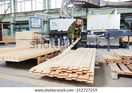 Worker of wood processing manufacture operating on woodworking machine