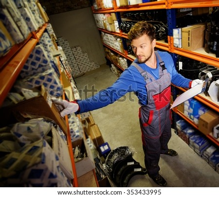 Worker on a automotive spare parts warehouse  - stock photo