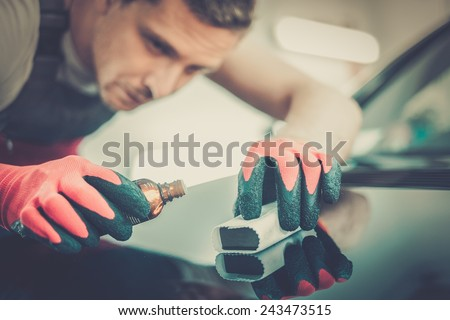 Worker on a car wash applying nano coating on a bonnet  - stock photo