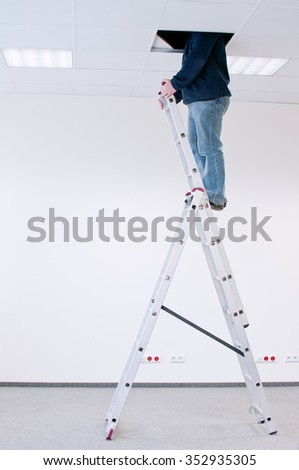 worker on a ladder, peering through a hole in the ceiling