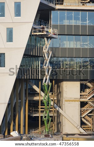 Worker on a Scissor Lift at a construction site - stock photo