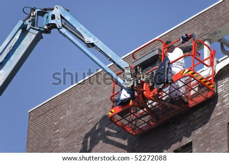 Worker on aerial access platform - stock photo