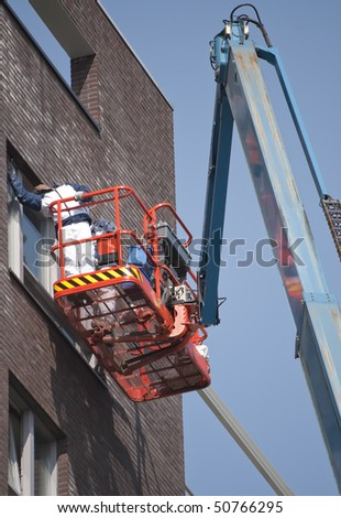 Worker on aerial access platform painting window frame - stock photo