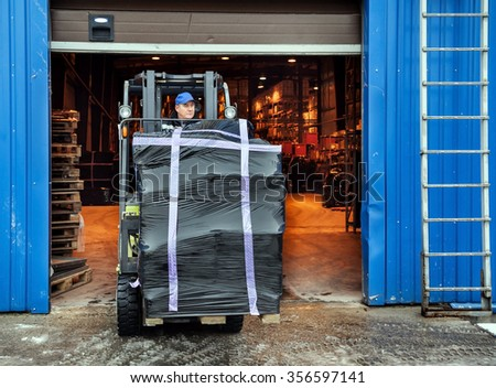 Worker on forklift transporting cargo on large modern warehouse - stock photo
