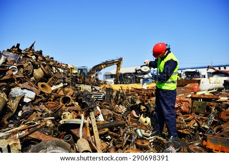 Worker on junkyard. Copy space available. - stock photo