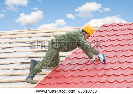 worker on roof at screwdriving works with metal tile and roofing iron - stock photo