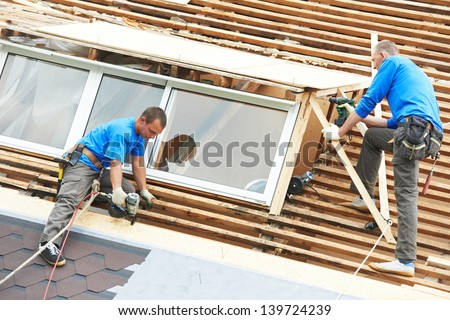 worker on roof at works with flex tile material mounting roofing - stock photo