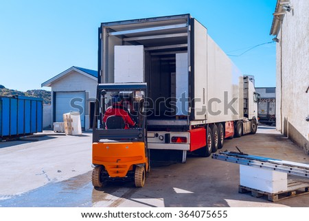 Worker on the loader loads long white semi-truck  - stock photo