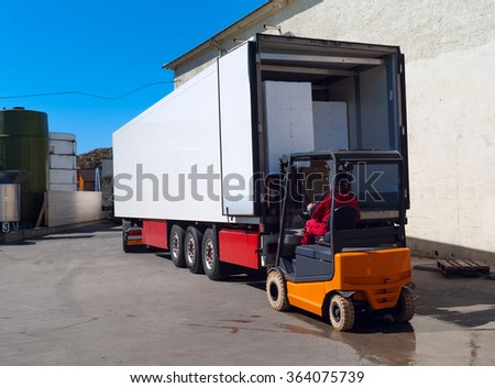 Worker on the loader loads white semi-truck  - stock photo
