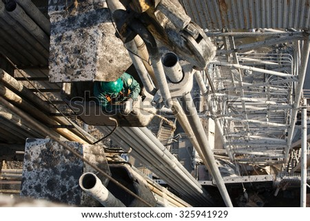 worker on the Oil derrick - stock photo