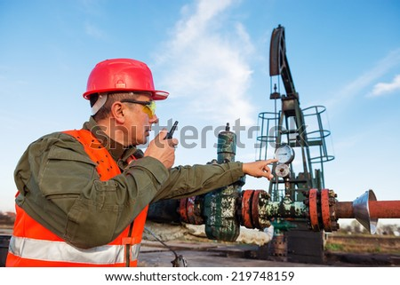 Worker on the oil field , pointing at pumpjack in the background.Refinery, oil and gas  - stock photo