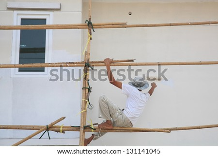 Worker on wooden scaffold painting wall of construction building - stock photo