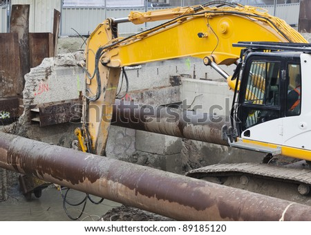 Worker operating excavator equipped with demolition hammer during the destruction of a reinforced concrete wall - stock photo