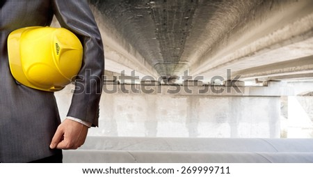 worker or engineer holding in hands yellow helmet for workers security on background of  new concrete bridge and metal tube over river in perspective buildings gray idea building new road junctions - stock photo