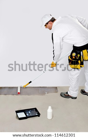 worker paint with primer concrete floor for waterproofing - stock photo
