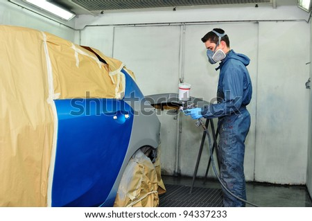 Worker painting a blue car. - stock photo