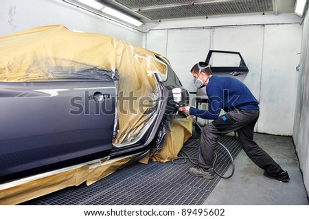 Worker painting a car. - stock photo