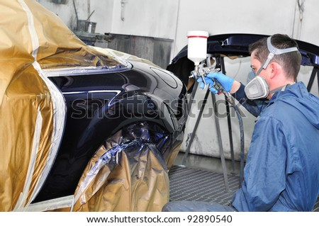 Worker painting a car - stock photo