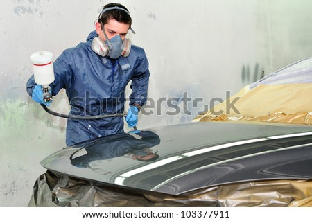 Worker painting a car in a paint booth,