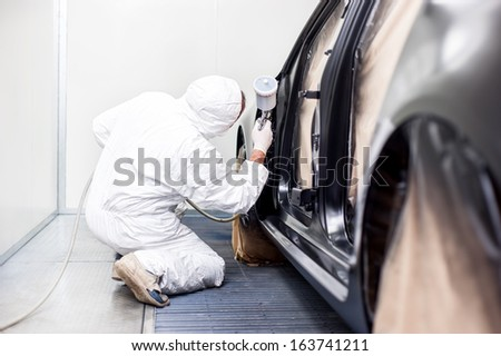 worker painting a car in a special painting box, wearing a white costume and a breathing helmet as protection gear - stock photo