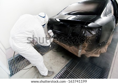 Worker painting a car in garage using an airbrush gun - stock photo