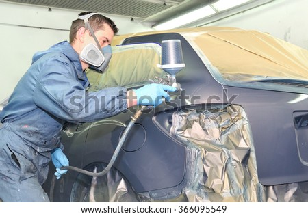 Worker painting a gray car in a paint chamber. - stock photo