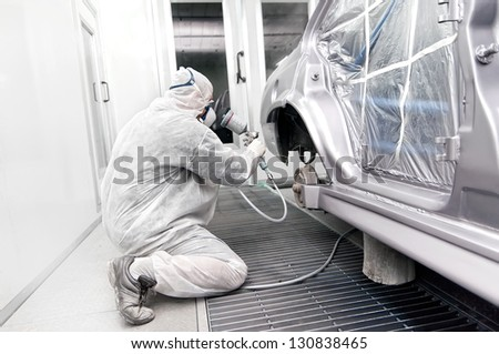 worker painting a grey car in a special garage, wearing a white costume