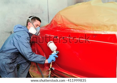 Worker painting a red car.