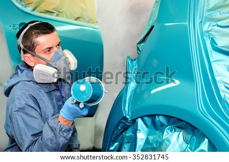 Worker painting blue car in body shop. - stock photo