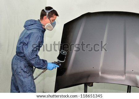 Worker painting car bonnet. - stock photo