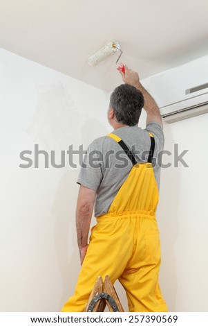 Worker painting ceiling to white color with paint roller - stock photo