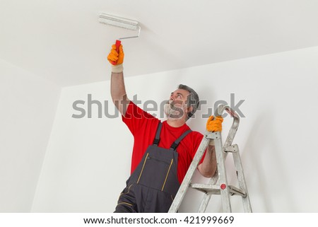 Worker painting ceiling with paint roller from ladder - stock photo