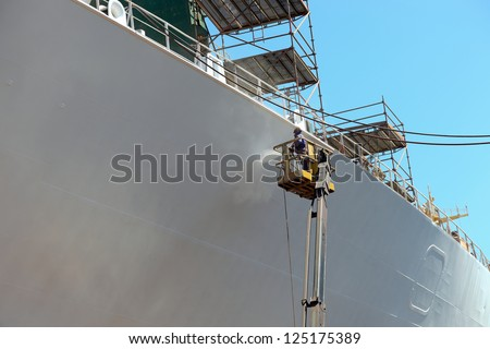 Worker painting ship hull using airbrush. - stock photo