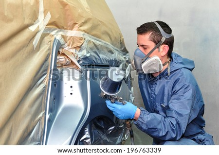 Worker painting silver car in a paint box.