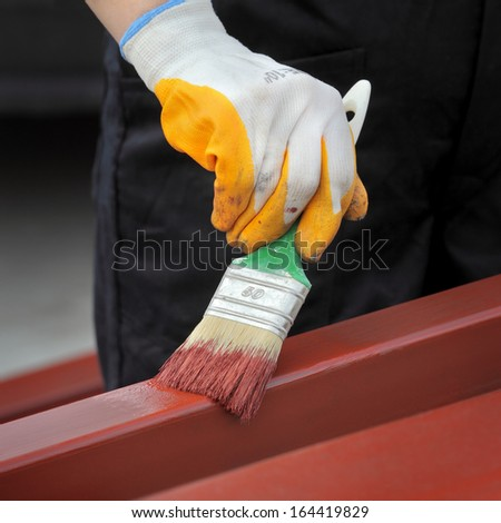 Worker painting  steel tube with paint brush selective focus on hand - stock photo