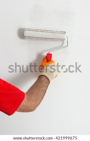 Worker painting wall to white with paint roller, closeup of hand