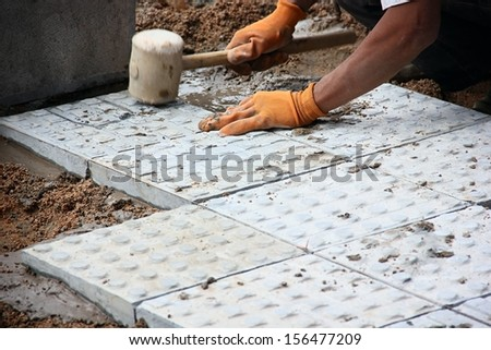 Worker paving tiles on street. - stock photo