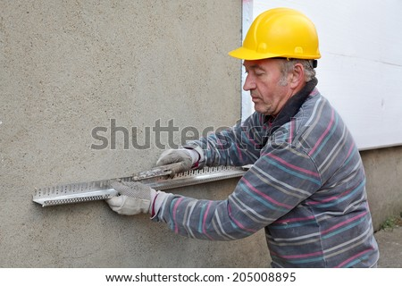 Worker placing aluminum batten for styrofoam sheet insulation to the wall - stock photo