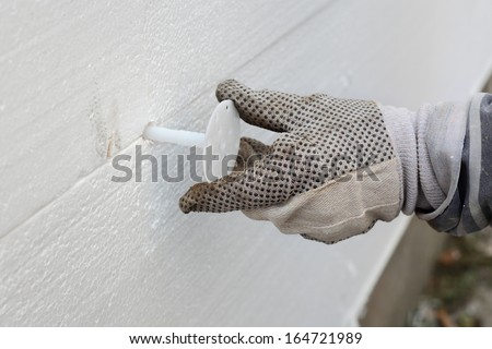 Worker placing expansion anchor to styrofoam sheet insulation of the wall - stock photo