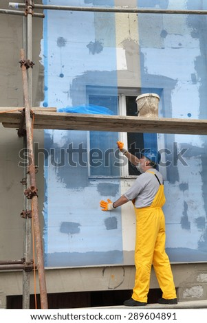 Worker placing mesh over styrofoam insulation and mortar - stock photo
