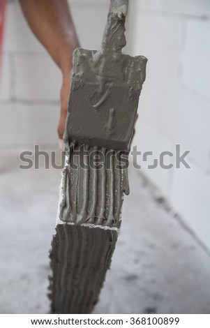 worker plastering lightweight Concrete block, Foamed concrete block, raw material for industrial wall or house wall - stock photo