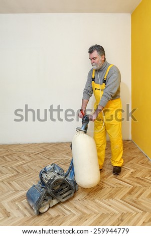 Worker polishing old parquet floor with grinding machine - stock photo