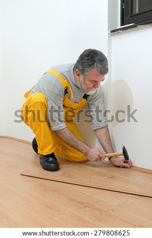 Worker pound in a nail to batten for laminate floor, hammer nail,  floating wood tile