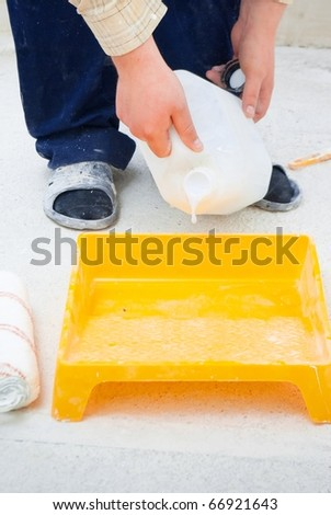 worker pouring paint from a large bucket - stock photo