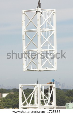 Worker prepares to join crane tower sections with CN tower in background - stock photo