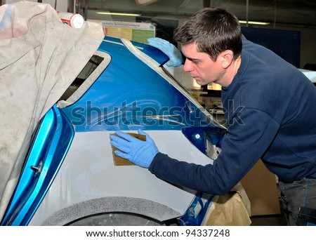 Worker preparing body part for paint. - stock photo