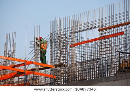 Worker preparing steel rods to concrete - stock photo