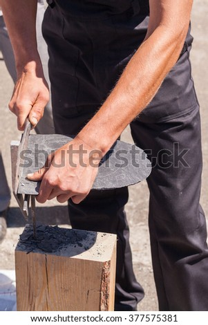 Worker produces roofing slate using a slate hammer - stock photo