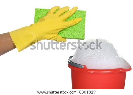 Worker protecting hand from detergents as they use a cleaning sponge and a soapy bucket of detergent.